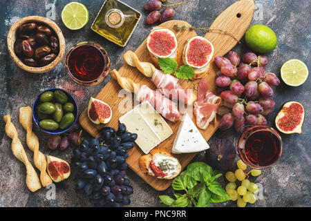 A variety of snacks, prosciutto,grapes, wine, cheese with mold, figs, olives on a rustic background. Top view,flat lay - Stock Photo