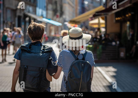 A couple of people with backpacks walking along the street. View from the back.
