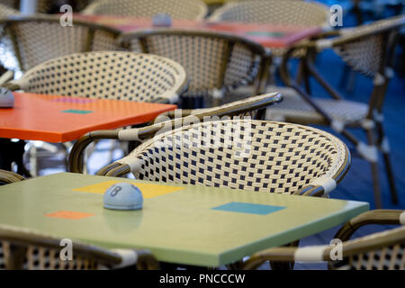 Wicker chairs and colorful tables in the outdoor cafe. - Stock Photo