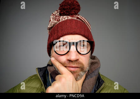 Portrait of amature funny man wearing warm hat in pensive mood. How to protect yourself from winter weather thinking. - Stock Photo