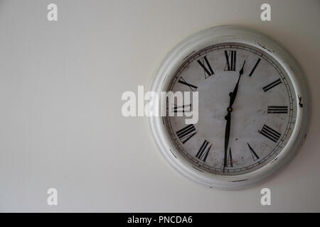 White Vintage Clock on a cream wall set to lunch time (12.30) - Stock Photo