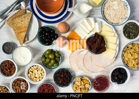 Healthy and various morning breakfast selection:  eggs, olives, cereals, ham, cheeses, bread, nuts, fruits, berries on the white wooden table, selecti - Stock Photo