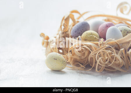 Coloured chocolate eggs in nest made from wood shavings close up, selective focus. Warm pastel toned macro photo - Stock Photo