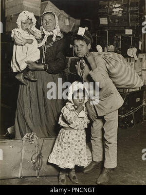 Immigrant Family in the Baggage Room of Ellis Island. Date/Period: 1905. Gelatin silver print. Width: 19.1 cm. Height: 24.1 cm (sheet). Author: Lewis Hine. - Stock Photo