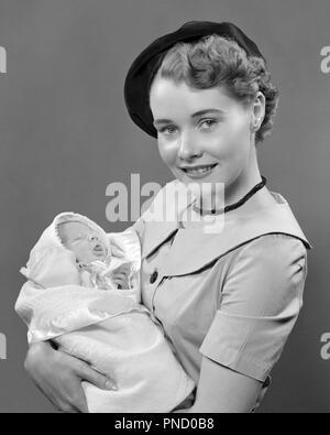 1950s PORTRAIT SMILING YOUNG WOMAN MOTHER WEARING BERET HAT LOOKING AT CAMERA HOLDING INFANT BABY SON IN ARMS  - b5169 HAR001 HARS URBAN MOTHERS OLD TIME NOSTALGIA HUGGING OLD FASHION 1 JUVENILE STYLE YOUNG ADULT INFANT EMBRACE SONS PLEASED JOY LIFESTYLE CELEBRATION FEMALES STUDIO SHOT HEALTHINESS HOME LIFE HALF-LENGTH HUG LADIES PERSONS CARING MALES EMBRACING B&W EYE CONTACT HAPPINESS TIGHT CHEERFUL PRIDE IN SMILES CONNECTION JOYFUL STYLISH BABY BOY BERET JUVENILES MOMS TOGETHERNESS YOUNG ADULT WOMAN BLACK AND WHITE CAUCASIAN ETHNICITY HAR001 OLD FASHIONED - Stock Photo