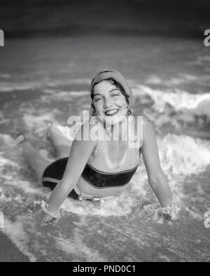 1920s SMILING BRUNETTE WOMAN LYING IN BEACH SURF WAVES WEARING BATHING CAP SWIMSUIT LOOKING AT CAMERA - b5831 HAR001 HARS LADIES PERSONS SURF B&W EYE CONTACT BRUNETTE SHORE HAPPINESS CHEERFUL HIGH ANGLE STYLES EXCITEMENT RECREATION BEACHES SMILES JOYFUL STYLISH BATHING SUIT FASHIONS SEASHORE YOUNG ADULT WOMAN BLACK AND WHITE CAUCASIAN ETHNICITY COASTAL HAR001 OLD FASHIONED