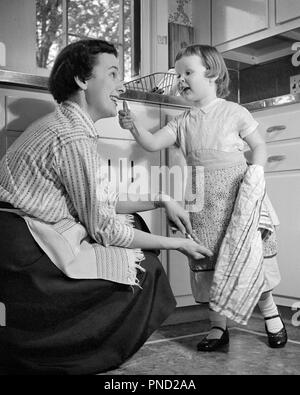 1950s LITTLE GIRL AND MOTHER IN KITCHEN BOTH WEARING APRONS GIRL HOLDING DISH TOWEL GESTURING TO MOTHER - j8225 HBB001 HARS OLD TIME BUSY NOSTALGIA GOOD OLD FASHION 1 TOWEL JUVENILE STYLE COMMUNICATION LAUGH DISH TEAMWORK PLEASED JOY LIFESTYLE FEMALES HEALTHINESS HOME LIFE FULL-LENGTH LADIES DAUGHTERS PERSONS CARING CONFIDENCE GESTURING APRONS B&W HOMEMAKER HAPPINESS HOMEMAKERS CHEERFUL BOTH AND EXCITEMENT MARY JANE HOUSEWIVES SMILES CONNECTION HELPFUL JOYFUL STYLISH THUMBS UP BEHAVIOR GROWTH JUVENILES MID-ADULT MID-ADULT WOMAN MOMS TOGETHERNESS BLACK AND WHITE CAUCASIAN ETHNICITY - Stock Photo