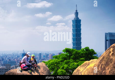April 1, 2018.  Taipei, Taiwan.  A mother and daughter posing on rocks with Taipei 101 landmark building rising above generic architecture in the city - Stock Photo