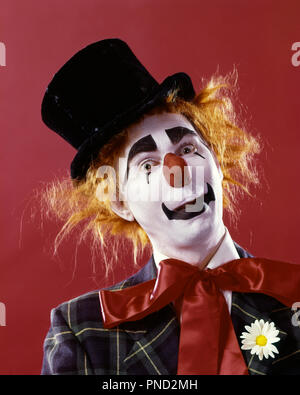 1970s SILLY WHITE FACE RED NOSE CLOWN LOOKING AT CAMERA WEARING TOP HAT ORANGE HAIR WIG PLAID JACKET AND RED RIBBON NECK TIE  - kc5322 PHT001 HARS CONFIDENCE ORANGE EXPRESSIONS EYE CONTACT BIZARRE SUCCESS PERFORMING ARTS HAPPINESS WEIRD PERFORMER AND EXCITEMENT ZANY UNCONVENTIONAL OF ENTERTAINER OCCUPATIONS WHITEFACE COULROPHOBIA ACTORS NECK TIE STYLISH IDIOSYNCRATIC AMUSING ECCENTRIC ENTERTAINERS MID-ADULT MID-ADULT MAN PERFORMERS TOP HAT YOUNG ADULT MAN CAUCASIAN ETHNICITY ERRATIC OLD FASHIONED RED NOSE - Stock Photo