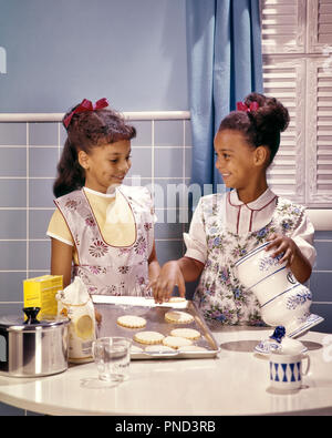 1960s TWO SMILING AFRICAN AMERICAN GIRLS SISTERS IN KITCHEN BAKING COOKIES  - kj5134 PHT001 HARS COPY SPACE HALF-LENGTH INSPIRATION COOKIES SIBLINGS CONFIDENCE SISTERS APRONS SUCCESS HAPPINESS WELLNESS AFRICAN-AMERICANS AFRICAN-AMERICAN EXCITEMENT KNOWLEDGE RECREATION AFRICAN ETHNICITY SIBLING SMILES BAKERS BLACKS COOKS HAIR RIBBONS JOYFUL STYLISH COOPERATION HAIR RIBBON JUVENILES KITCHENS TOGETHERNESS OLD FASHIONED AFRICAN AMERICANS - Stock Photo
