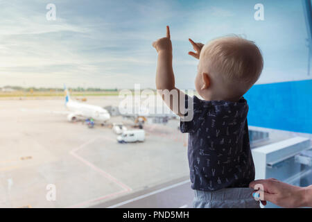 Little boy at airport looking out window at airplane. - Stock Photo