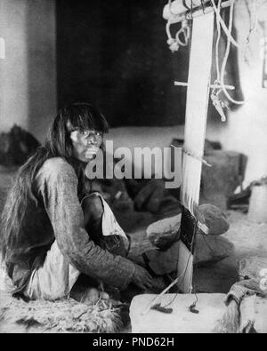 1890s 1898 NATIVE AMERICAN INDIAN MAN LOOKING AT CAMERA WEAVING CEREMONIAL KILT ON LOOM  - q73416 CPC001 HARS PRECISION WEAVE WEAVING YOUNG ADULT MAN BANGS BLACK AND WHITE CEREMONIAL KILT LOOM OLD FASHIONED WEAVER - Stock Photo