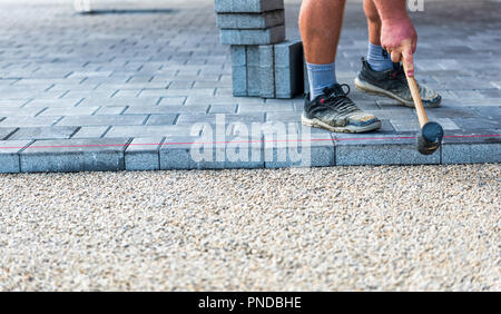 Laying gray concrete paving slabs in house courtyard driveway patio. Professional workers bricklayers are installing new tiles or slabs for driveway,  - Stock Photo