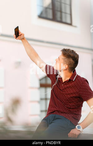 young businessman is taking a photo of a smartphone on the street. Selfie - Stock Photo