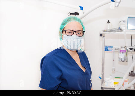 portrait of nurse with mask in surgery room - Stock Photo