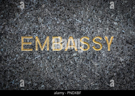 A Gold Embossed Embassy Sign On Marble - Stock Photo