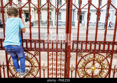 London England Great Britain United Kingdom Kensington Natural History Museum exterior Cromwell Road entrance fence boy child climbing - Stock Photo