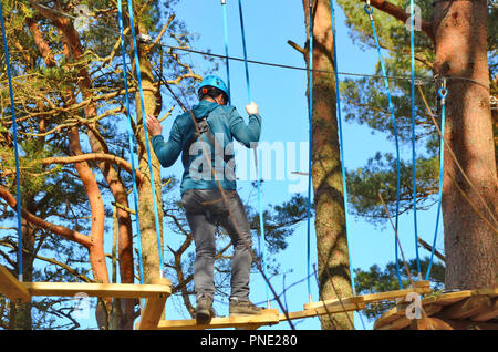 Young man on the high tree tops rope course in Glenshee , Scotland. - Stock Photo