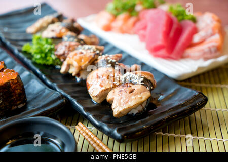 Sushi with chopsticks and soy sauce. Sushi roll japanese food in restaurant. Foie Gras Sushi set with salmon, tuna, flying fish roe and caviar closeup - Stock Photo