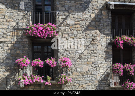 A front view of a stone facade with four black iron railing balconies with violet hanging flower on them in Ainsa, a small rural village in Spain - Stock Photo