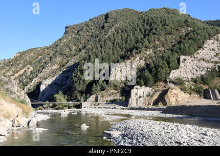 A landscape of Spanish Aragonese Pyrenees, with forest, mountains and an old wooden bridge which leads to Janovas, an abandoned town due to a dam - Stock Photo
