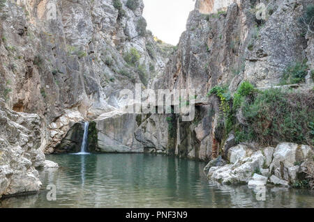 A rural landscape of a small lake and Aguavivas river waterfalls inside a rocky canyon dug by the warer, at the sunset, in the Aragon region, Spain - Stock Photo