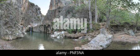 A rural landscape of a small lake and Aguavivas river waterfalls inside a rocky canyon dug by the water, and a stone bridge, at the sunset, in Spain - Stock Photo