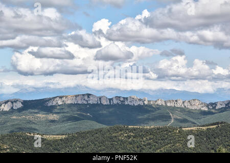 A summer landscape of the typical Pre-Pyrenees mountains from Puig Monè, with yellow grass and a blue cloudy sky in Luesia, a rural town in Spain - Stock Photo