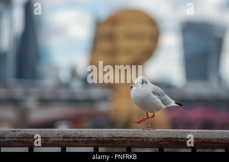 South Bank, London, UK. 21 September, 2018. Steuart Padwick's sculpture Head Above Water and City skyscrapers form a backdrop to a strolling seagull on a bright and breezy London day. Credit: Malcolm Park/Alamy Live News. - Stock Photo