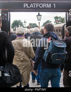 Kidderminster, UK. 21st September, 2018. Day two of Severn Valley Railway Autumn Steam Gala sees excited crowds flocking to the Kidderminster heritage railway station. Despite the disappointing weather and persistent rain showers, railway enthusiasts take every opportunity to take a train ride on the visiting UK steam locomotives. Rail passengers are seen here, rear view, rushing to the platform in a hurry to board the waiting train. Credit: Lee Hudson/Alamy Live News - Stock Photo