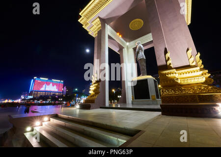 Statue of King Norodom Sihanouk in park with Cambodian flag projected by neon light in the background. In Preach Suramit Boulevard in Phnom Penh, Camb - Stock Photo
