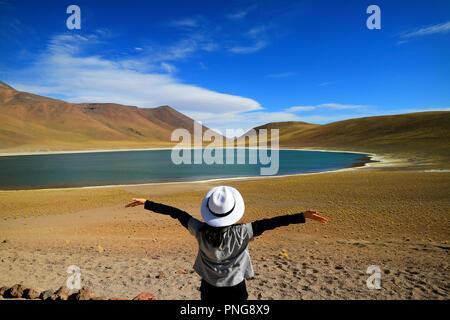 Female tourist raising her arms admiring the amazing deep blue lagoon Laguna Miniques, located in the altiplano of Antofagasta region, Chile - Stock Photo