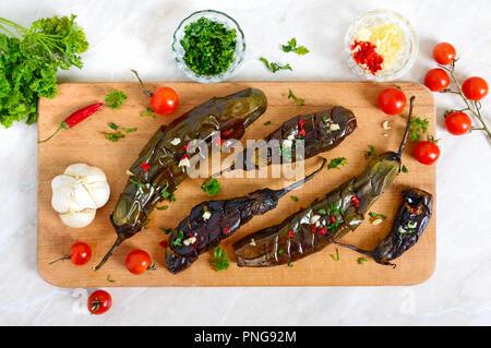 Baked eggplant, garlic, fresh herbs - ingredients for a snack 'Melindzano'.  Eggplant salad. Traditional greek, Mediterranean cuisine. - Stock Photo