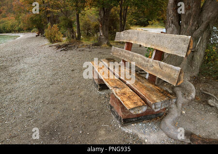 Rustic Wooden Bench Made of Timber Logs on the Lake Shore Among Fall Foliage in Tierra del Fuego National Park, Patagonia, Argentina - Stock Photo