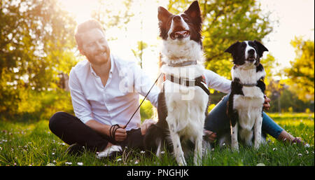 Beautiful couple walking dogs and bonding in nature - Stock Photo