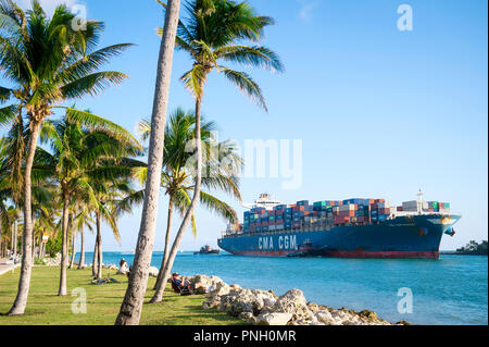MIAMI, USA - CIRCA AUGUST, 2018: Container freight ship 'CMA CGM MUSSET' entering port through a narrow, palm-lined channel at the tip of South Beach - Stock Photo