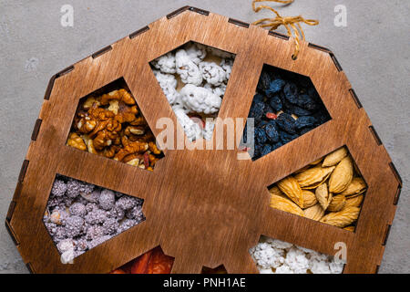 Mixed Nuts on grey background, as apricot, raisins, walnuts, goji, peanuts in glaze, almonds Healthy food and snack. vitamins, fiber, pectin, iron, po - Stock Photo