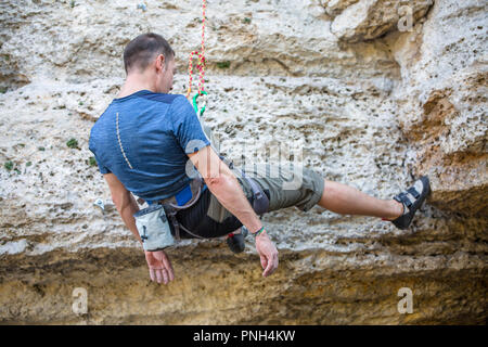 Photo from back of climbing sports man on rock - Stock Photo