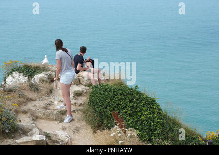couple enjoying the views from porte d Aval, Etretat, Normandy France - Stock Photo