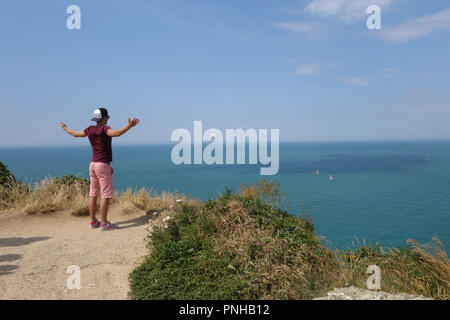 young man enjoying the view from porte d Aval, Etretat, Normandy France - Stock Photo