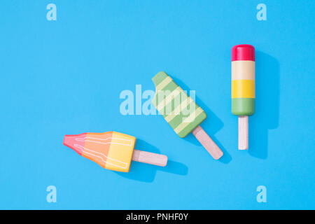 Three wooden toy ice lollipops popsicles on a pastel blue background with space for copy and text with minimalist composition - Stock Photo