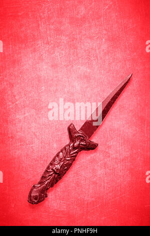 Red Wicca wiccan dagger on a red textured background with space for copy and text.  Ceremonial blade for spiritual rituals - Stock Photo