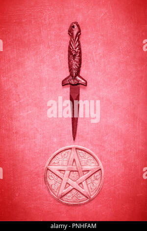 Black wicca wiccan dagger with pentagram on a textured red background.  Ceremonial blade and pentagram for spiritual rituals - Stock Photo