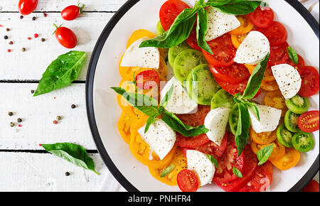 Mozzarella cheese, tomatoes and basil herb leaves in plate on the white wooden table. Caprese salad. Italian food. Top view - Stock Photo