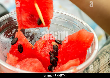 Pieces of juicy red watermelon with bones in a plastic cup. Close-up. - Stock Photo