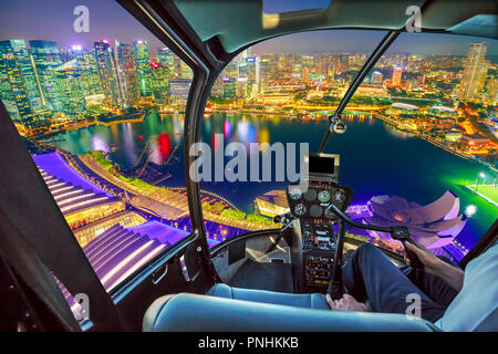 Helicopter cockpit interior flying on Singapore marina bay with financial district skyscrapers at night reflected on the harbor. Scenic flight above Singapore skyline. Night urban aerial scene. - Stock Photo