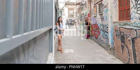 Teen and woman leaning against building in street with buildings covered with graffiti - Stock Photo