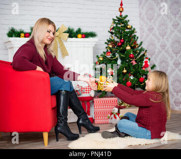 Portrait of brunette mom and little daughter giving presents each other for x mas and new year holidays. Happy family of mother with pretty girl celebrating Christmas - Stock Photo
