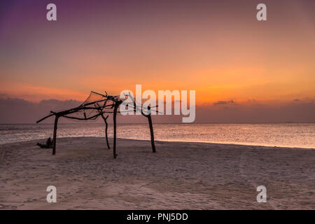 Colorful sunset in a deserted island, small wood hut, no one around - Stock Photo