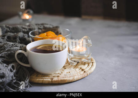 Still life details in home interior of living room. Cup of tea and dried apricots on a table, candles and knited blanket. Cozy mood autumn or winter i - Stock Photo